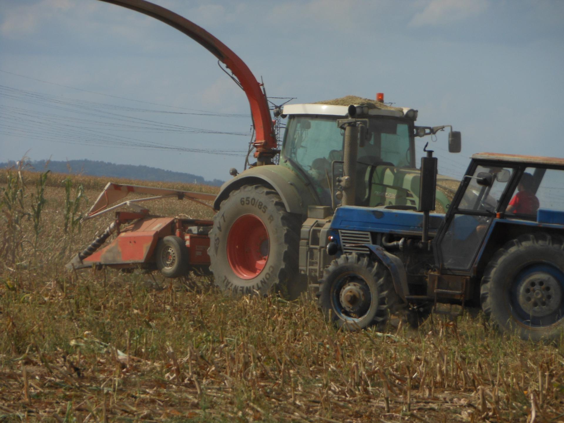 Traktor FENDT 930 s otočným řízením agregován s nesenou řezačkou s adaptérem na kukuřici.JPG